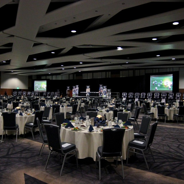 Ballroom with formally set tables and a stage with banners