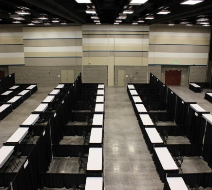 Rows of exhibitor booths with a table