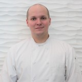 Photo of a male wearing a white chefs coat.