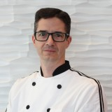 Photo of a male with dark hair wearing chef attire and thick-rimmed glasses.